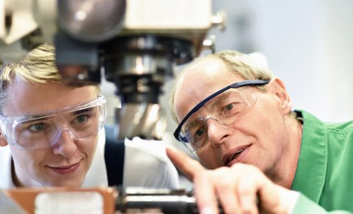 closeup picture: trainer and apprentice in vocational training on a milling machine - teacher explains details of the machine